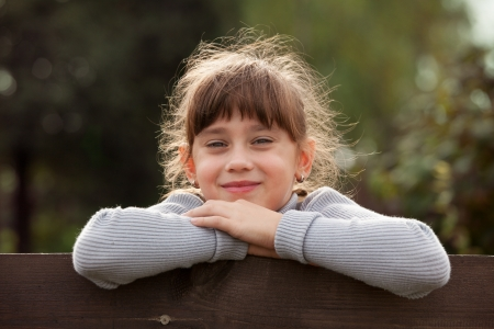 Charming little girl leaning on a fence Stock Photo - 17276782