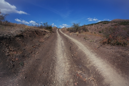 swelter: Dusty dirt road going up on a hot afternoon Stock Photo