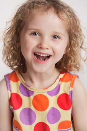mirth: Cheerful little girl in a smart dress Stock Photo