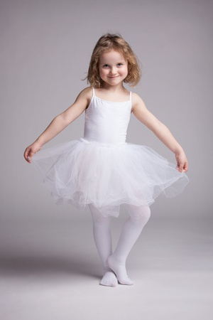 Happy little girl in white dress ballerina photo