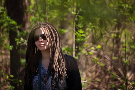 Stylish girl with dreadlocks in the trees photo