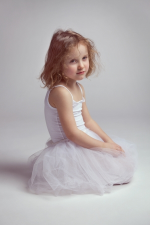 Little girl - ballerina sitting on the floor photo
