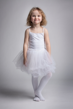 Happy little girl in a white ballet dress photo