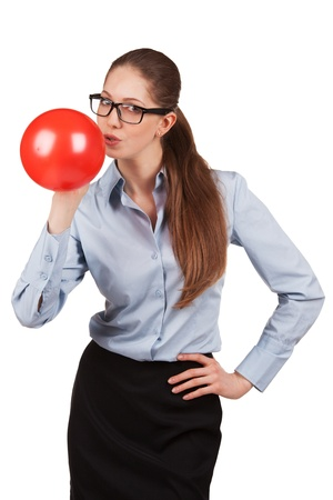 Beautiful girl with glasses inflating a red ball photo