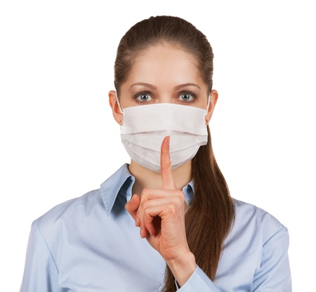 Woman in protective medical mask with a finger to his mouth photo