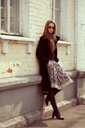 Stylish fashion model in a black coat leaning on a wall