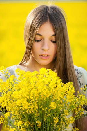 Cute young woman with a bouquet of yellow wildflowers photo