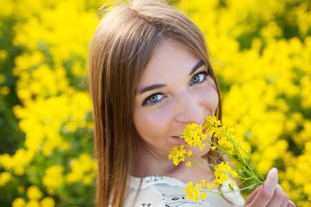 Cheerful girl smelling yellow wildflower summer day photo