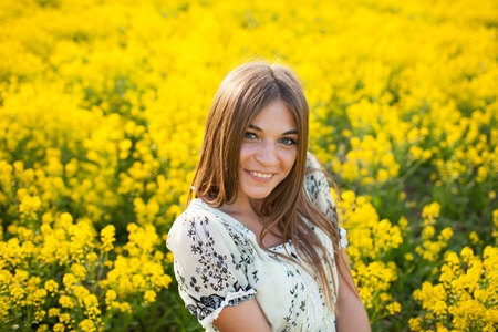 blessedness: Beautiful young woman among yellow flowers in a field