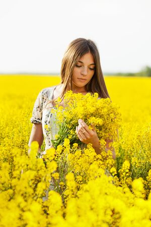 Girl with long hair holding a bouquet of yellow flowers photo