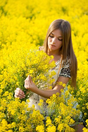 Beautiful girl with a bouquet in the field of yellow flowers photo