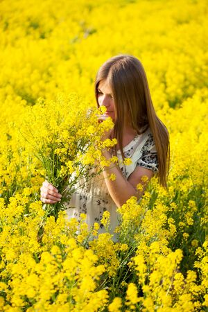 beatitude: Girl with a bouquet in the field of yellow flowers Stock Photo