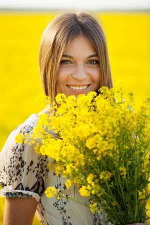 Smiling girl with a bouquet of wild flowers