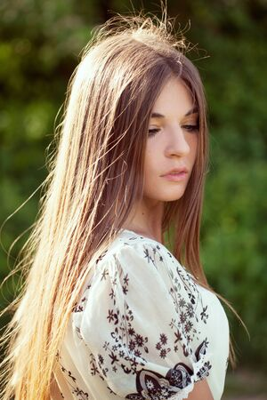 eyes downcast: Beautiful long-haired girl standing with downcast eyes