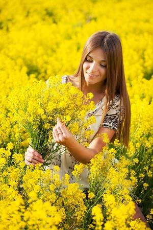 Beautiful girl gathers a bouquet of yellow wildflowers photo