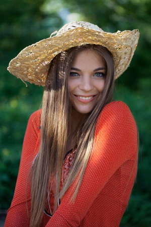 honey blonde: Cute smiling girl in a straw hat