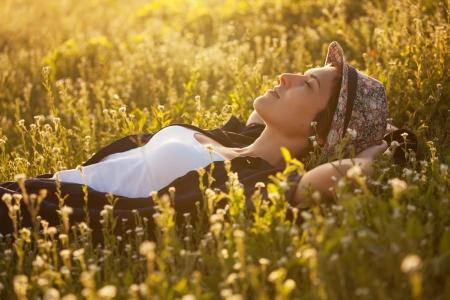Het meisje in een hoed dremet onder wilde bloemenpracht bij zonsondergang Stockfoto
