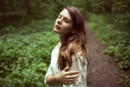 ennui: Unhappy girl standing in the middle of a dark forest