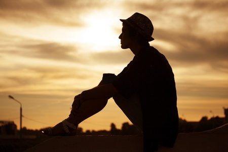 pacification: Silhouette of a girl in a hat against the evening sun Stock Photo