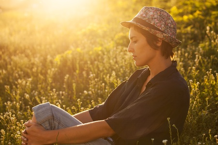 quietly: Girl sitting in the grass on a sunny evening Stock Photo