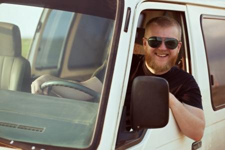 taxista: Programa piloto sonriente con gafas de sol que conduce un coche