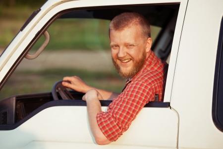 taxista: Programa piloto sonriente en una camisa roja durante la conducci�n