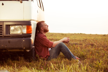 Bearded driver resting in a field near his car Stock Photo
