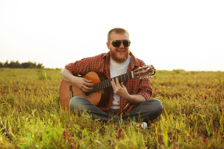 Man in jeans sits on grass and plays guitar Stock Photo - 21385722