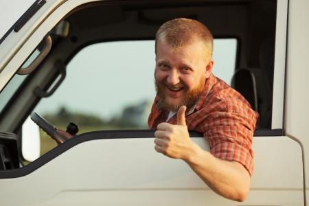 řidič: Řidič se vyklonil z kabiny a ukazuje, že to všechno v pohodě Reklamní fotografie