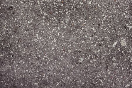 Road surface of asphalt interspersed with gravel photo