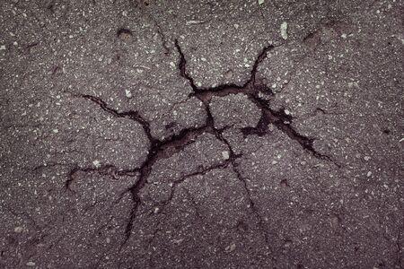 Piece of asphalt with cracks on the surface photo