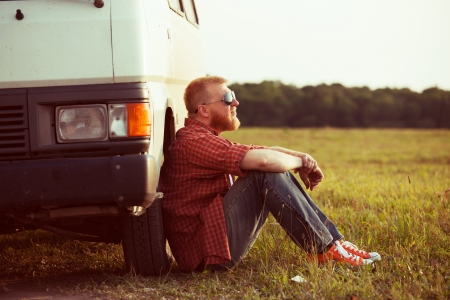 trucker: Driver sits next to his car in a field