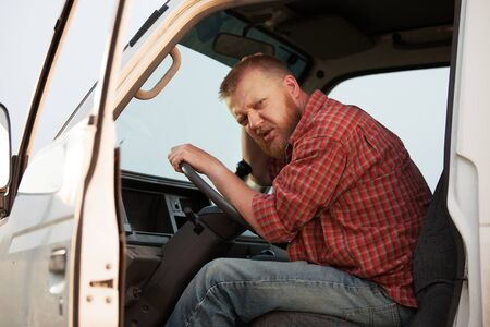 chofer: Algo desconcertado conductor barbudo en la cabina de su cami�n Foto de archivo