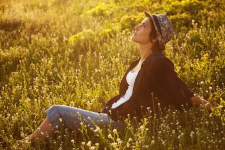 beatitude: Girl sits among the wild flowers on a summer evening