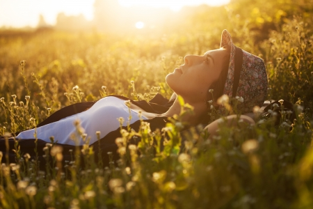 Happy girl lies among the wild flowers on a summer evening