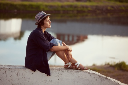 beatitude: Young woman in a hat sits and rests Stock Photo