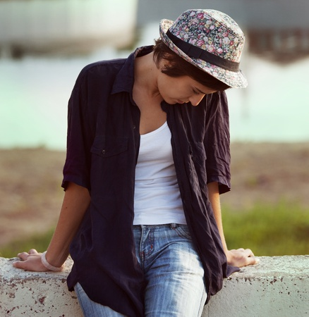 Lonely sad girl in hat and jeans