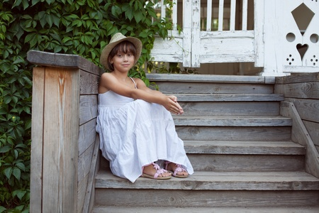 Cute little girl is sitting on the porch steps photo