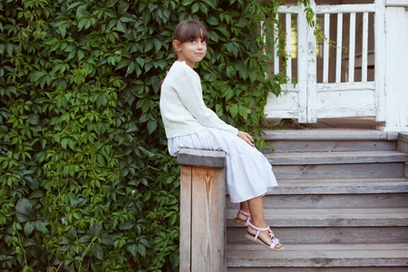 Beautiful little girl in dress sitting on the porch photo