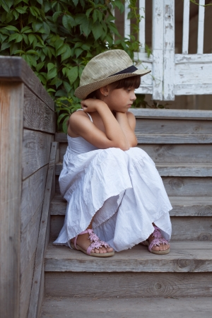 Sad little girl sitting alone on the porch photo