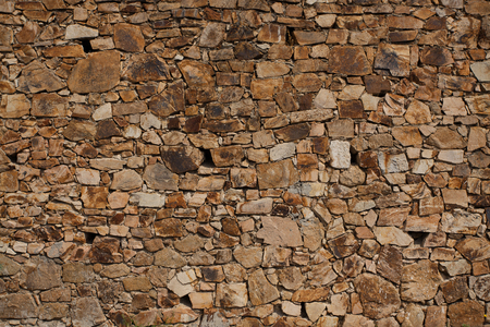 Sturdy old wall from a rough raw stone Stock Photo - 23247589