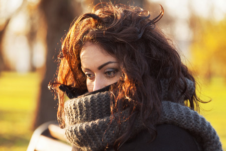 Sad, dark-haired woman wrapped in a scarf