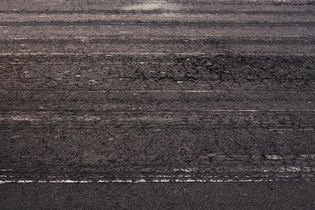 hardwearing: Asphalt road surface with traces from cars