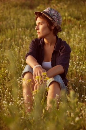 quietly: Young woman in hat sitting among wildflowers Stock Photo