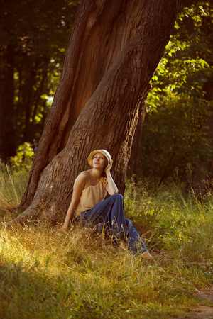Romantic young woman sitting under a big tree photo