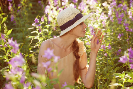 Young beautiful woman enjoying the scent of wildflowers
