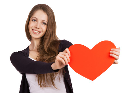 Beautiful cheerful girl with a red heart in the hands