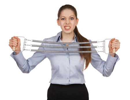 volition: Young woman trying to stretch the metal expander Stock Photo