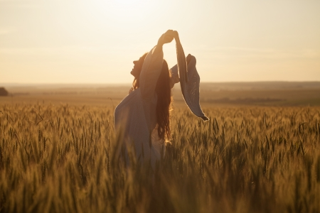 Happy young woman with a shawl in field