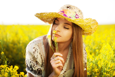 elation: Happy girl in a hat enjoying the smell of the flower Stock Photo